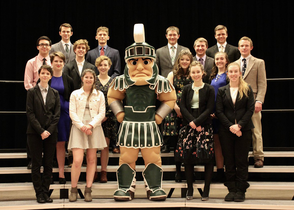 Sixteen high school students from Wyoming and the Upper Peninsula of Michigan pose with Sparty the mascot.